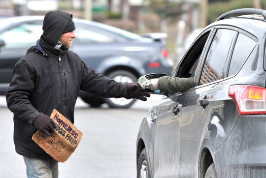 Jeff Davis, 39, receives a few dollars from a motorist while panhandling on the I-375 service drive near Larned in Detroit on April 1, 2020. He's been homeless, on and off, for about three years after getting laid off and divorced. Then his apartment caught on fire and he had no apartment insurance.