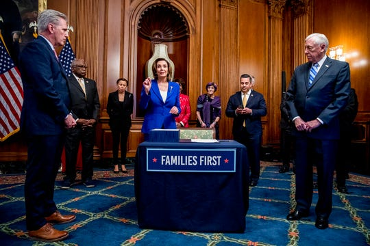 House Speaker Nancy Pelosi of Calif., center, prepares to sign the Coronavirus Aid, Relief, and Economic Security (CARES) Act after it passed in the House on Capitol Hill in this March 27, 2020, file photo.