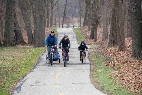 (From left) Jim Mong, his wife Susannah, and eight-year-old daughter Kean ride their bikes together at Kensington Metropark, in Milford, April 1, 2020.