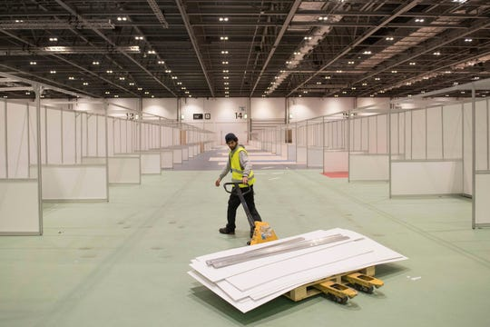 In this photo taken on Tuesday, March 31, 2020, work continues at the ExCel centre which is being made into a temporary hospital, in London. The new hospital, the NHS Nightingale, will comprise of two wards, each of 2,000 people, to help tackle coronavirus.