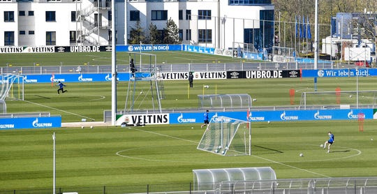 Due to the coronavirus outbreak at most two players of the German first division, Bundesliga, soccer club Schalke 04 exercise together to keep distance during the training on the club's training ground.
