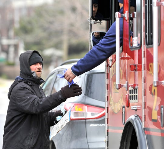 The Detroit Fire Department Fire Engine Operator of Squad 2 gives homeless man Jeff Davis a pair of protective gloves after giving him a protective mask.