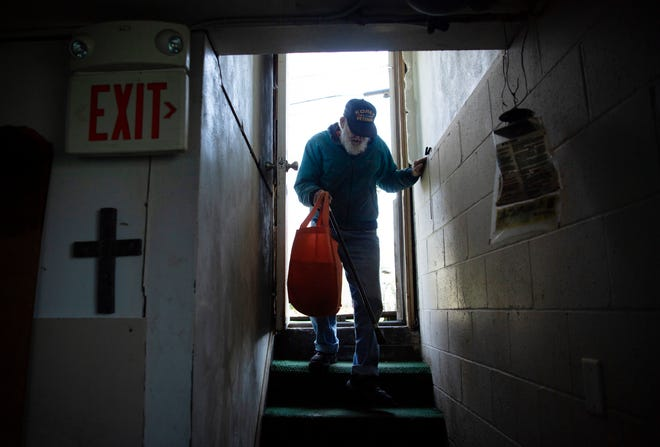 John Cambron gingerly makes his way down the stairs of the First Ebenezer Baptist Church to pick up lunch in Evansville, Ind., Wednesday afternoon, April 1, 2020. The church has been serving lunches for those in need for years, but has had to change their normal setup due to the coronavirus pandemic.