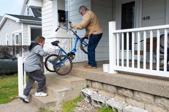 Ryan Green, left, and stepfather Bill Stinson puts Green's trike on their porch after a ride Wednesday afternoon, April 1, 2020. Green has Down's Syndrome and since school has been out due to the COVID-19 pandemic he has been riding every day. After his mother, Soni Stinson,  wrote about the theft on social media numerous people reached out to help and one anonymous person purchased a new trike for Green which will arrive on April 7th. Green's original trike was returned Tuesday evening after being found about 20 blocks from their home.