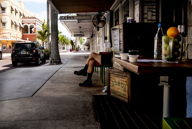 Scenes from downtown Fort Myers at the lunch hour on Sunday,  March 29, 2020. Businesses and restaurants are shuttered or are offering take out dining because of the coronavirus pandemic. Normally this sidewalk would be filled with lunchtime diners and tables.