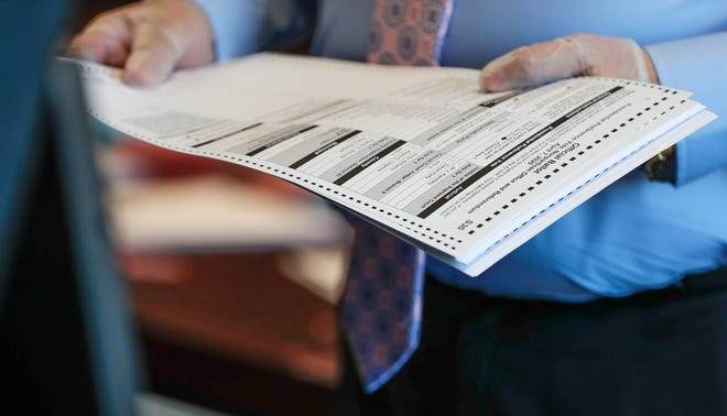 Clerk-Treasurer Patrick Moynihan Jr. processes absentee ballots on Wednesday, April 1, 2020, at Village of Ashwaubenon in Ashwaubenon, Wis. Ebony Cox/USA TODAY NETWORK-Wisconsin