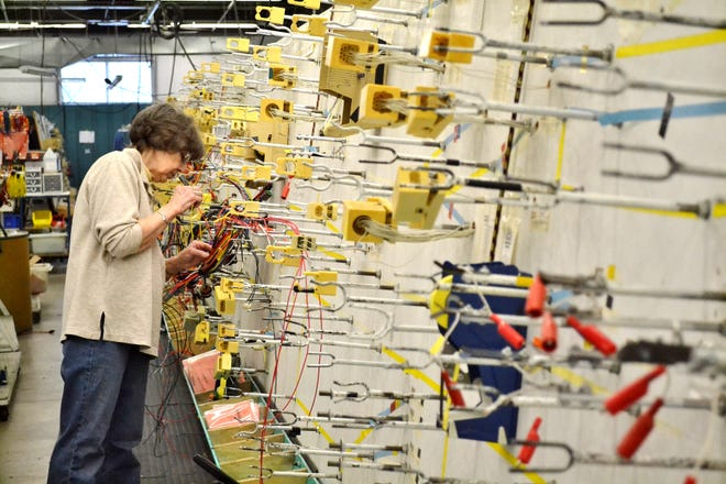 In this file photo from February 2016, Laurie Diehlmann works to assemble an electric wire harness at Unlimited Services in Oconto.