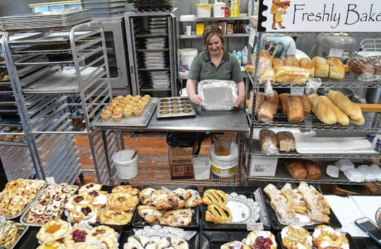Christine Jackson, left, looks over family of six ready made meals, near bread on a rack at the Village Bakery and Cafe in downtown Pendleton Wednesday.