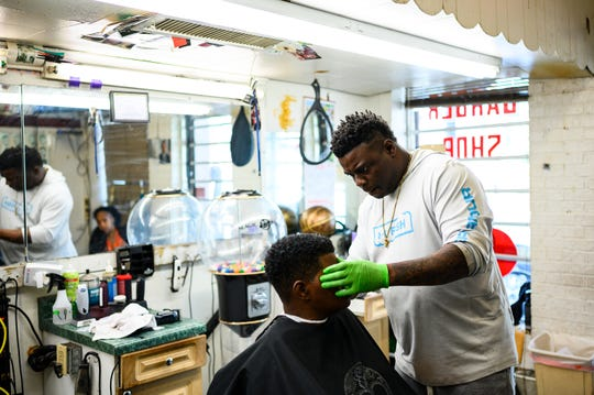 Bee Hughes cuts a customer's hair at Distinguished Gentleman 2 barber shop before the 5 p.m. deadline for non-essential businesses to close in South Carolina Wednesday, April 1, 2020.