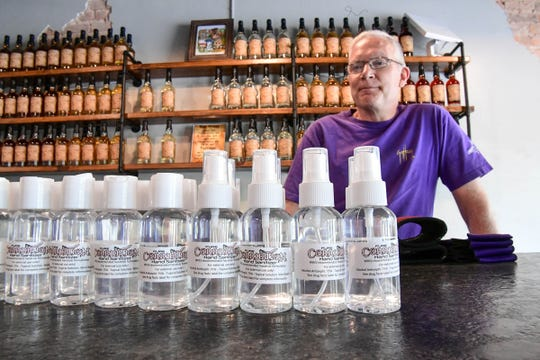 Ernie Wagner, owner of Swamp Fox Distilling in downtown Pendleton, looks over hand sanitizer he makes for local residents.