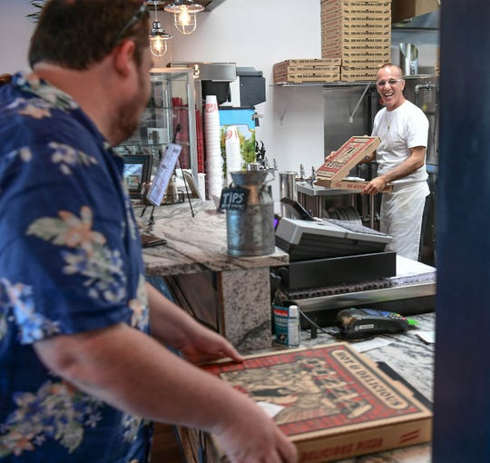Matt Rhodes, left, of Clemson buys a pizza take out order near chef Anthony Vicidomini of Brooklyn Pizza in downtown Pendleton Wednesday.