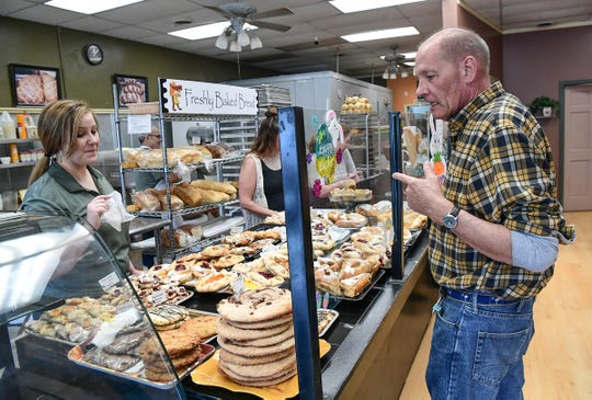 Doug Satzger, right, of Pendleton, orders pastry items from Christine Jackson at the Village Bakery and Cafe in downtown Pendleton Wednesday.
