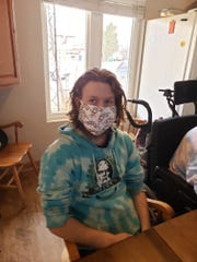 Shayden Bethel shows off a facemask donated to Quality Life Concepts by the Midway Hutterite Colony.