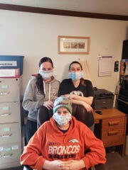 Jaime Disbrow, left and Tristan Johnson stand behind Ashley Huskins wearing facemasks donated to Quality Life Concepts by the Midway Hutterite Colony.