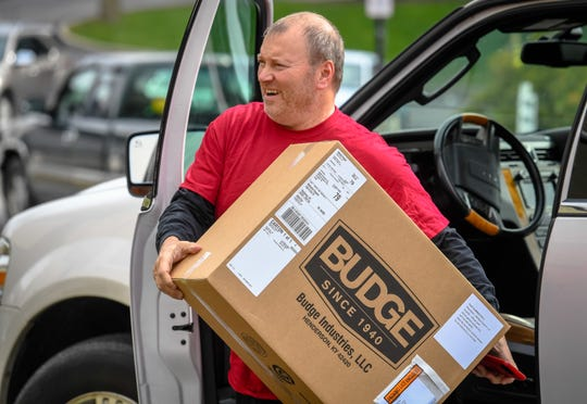 Frank Knight, with Budge Industries, gets out of his vehicle with a box of 500 masks his workers at their Henderson plant made, instead of their usual products of car and RV covers. Knight was delivering their first batch to Methodist Health in Henderson Tuesday, March 31, 2020.