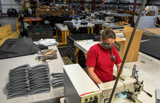 Budge Industries worker Heather Prater uses a sonic wielding machine to make the pleats for medical masks as workers at the Henderson plant convert to making masks instead of their usual products, car and RV covers Wednesday, April 1, 2020.