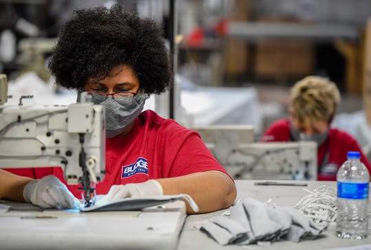 Workers at Henderson's Budge Industries, Lauretta Stewart-Blanks, left, and Crystal Baxter attach the elastic straps for medical masks as workers at the plant convert to making masks instead of their usual products, car and RV covers Wednesday, April 1, 2020.