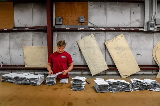 Russell Fuchs at Henderson's Budge Industries, counts the number of mask blanks they cut from a car cover as the plant converts to making masks instead of their usual products, car and RV covers Wednesday, April 1, 2020.