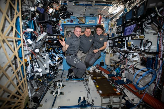 The Expedition 62 crew poses for a portrait aboard the International Space Station's U.S. Destiny laboratory module. Roscosmos Commander Oleg Skripochka, in the middle, is flanked by NASA Flight Engineers Andrew Morgan and Jessica Meir, Thursday, Feb. 20, 2020,