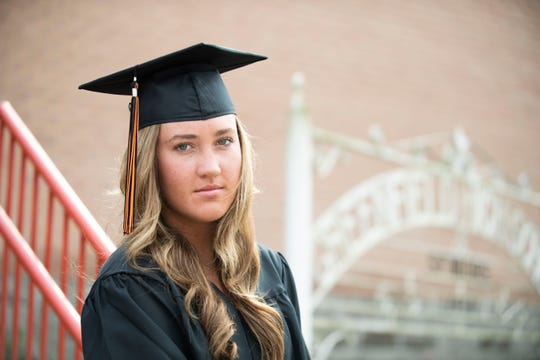 Greenfield senior Tess Darby wears her cap and gown. She puts them on in front of the Greenfield High school, Friday March, 27, 2020. Darby may not be able to walk during graduation due to the school delaying or cancelling any social activities due to the novel coronavirus, Covid-19.