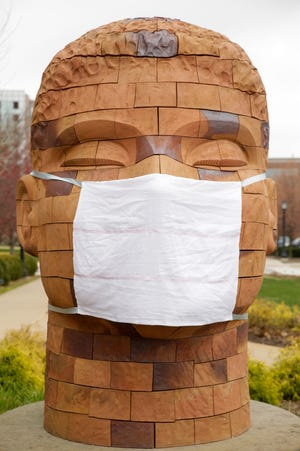 One of the two Brickhead statues by artist James Tyler is seen wearing a surgical mask outside Yue-Kong Pao Hall for Performing Arts, Wednesday, April 1, 2020 at Purdue University in West Lafayette.