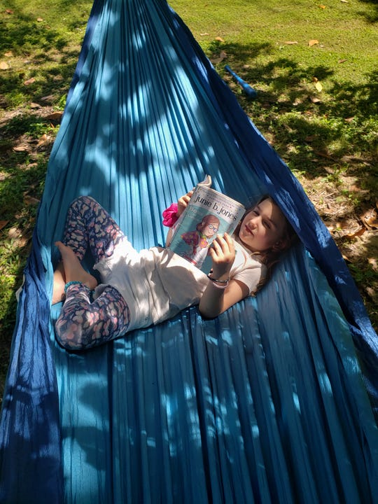 Broadmoor Elementary first-grader Audrey Broussard reads in a hammock at home while schools are closed to help stop the spread of COVID-19.