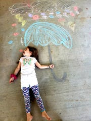 "Broadmoor Elementary first-grader Audrey Broussard poses with her sidewalk chalk art, pretending to eat ""candy rain."" The artwork was part of a distance learning activity."