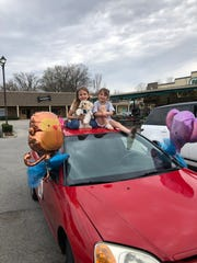 """Lali, left, and her younger sister, Aiya, with their dog, Gizmo, on the """"birthday express"""" car."""