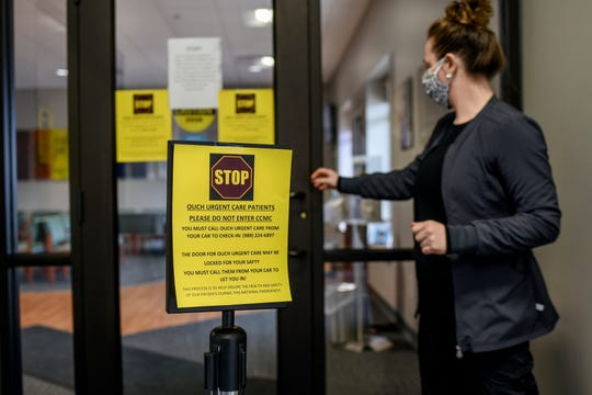 Radiologic technologist Samantha Jackson walks into OUCH Urgent Care on Tuesday, March 31, 2020, in St. Johns. A sign warns patients that they need to call the facility form their cars in order to get inside during the coronavirus pandemic.