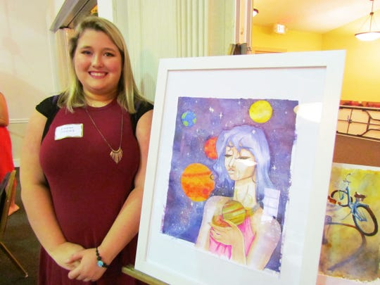 Emma Snow with a sample of her watercolors.