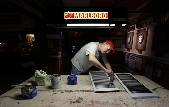 PJ Johnson, a bartender for 29 years at Wolski's Tavern, paints shutters on a tarp covered pool table at Wolski's Tavern,1836 N Pulaski St. in Milwaukee, on April 1. According to the popular bar's owner, Bernie Bondar, he and a few of his staff are using the closure due to the coronavirus to do some maintenance, deep cleaning and refinishing the floor - tasks that would have required the tavern to close anyway.