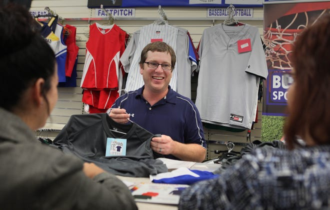 Brian Burghardt of Burghardt Sporting Goods helps customers with an order in this 2011 photo. The company is moving its headquarters to New Berlin.