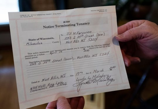 Jill Ferguson holds her eviction notice  at her home in West Allis.