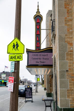 "The marquee outside the Avalon Theater in March reads: ""COVID-19 wasn't caused by Thanos (we think)."" The Bay View theater has remained closed, waiting for bigger movies and audiences ready to see them indoors."