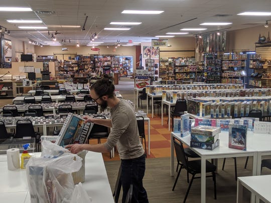 Andy Brown packs up board games at the empty Greenfield Board Game Barrister to be delivered to customers along with their food from Oak & Shield Gaming Pub. Staff are choosing games through Board Game Barrister's online personal shopper service.