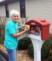 Lynn  Nickels is shown putting food in the Christ by the Lake Lutheran Church Little Free Library. The church recently removed its books to house non-perishable food during the coronavirus outbreak. Stocked with individual, instant-type food items such as mac-and-cheese cups, Ramen noodles and tuna packets, the box is at the south end of the church's parking lot at 1304 C.S. Woods Blvd. for those in need of food.
