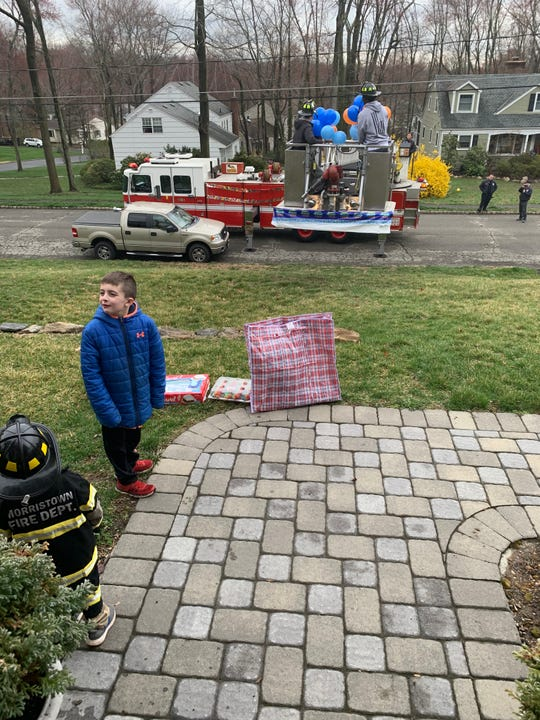 Justin and Jake Barter gather outside their Morris Township home as firefighters deliver treats and gifts in honor of Jason's third birthday.