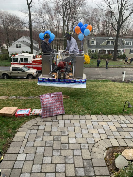 The Morristown and Morris Township Fire Departments deliver pizza, cupcakes and gifts for Jason Barter on his third birthday.