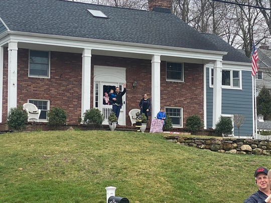 Morristown Fire Captain Phillip Barter waves at his colleagues as they surprise his son Jason on his third birthday.