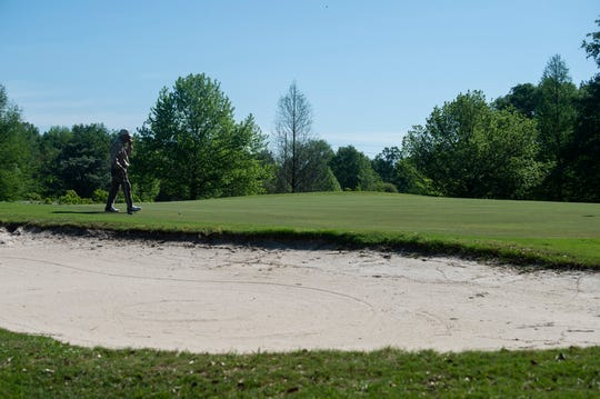 Ken Carlson walks to the green at Lagoon Park golf course in Montgomery, Ala., on Wednesday, April 1, 2020. The rakes have been removed from sand traps for sanitary reasons.