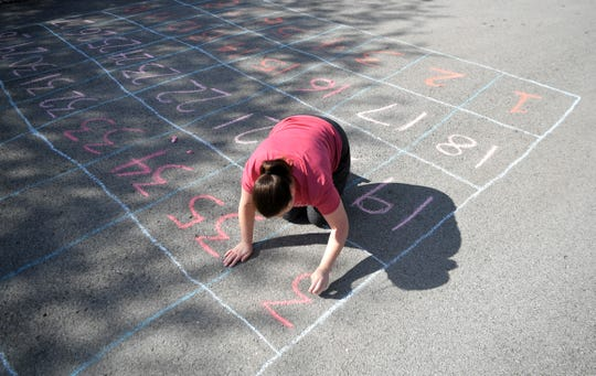 "Franklin's Forrest Crossing neighborhood has created a  ""social distancing calendar of fun."" Some residents, like Sarah Wilkerson, made a chalk Chutes and Ladders game on her street on Wednesday, April 1, 2020."