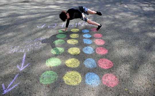 "Franklin's Forrest Crossing neighborhood has created a  ""social distancing calendar of fun.""  On Wednesday, some residents like Eli Ecken, 11, played Twister in the street."