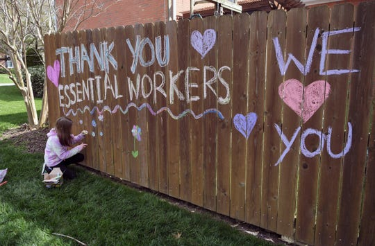 "Franklin resident Madelyn Wilkerson, 9, decorates her fence with chalk, creating messages of appreciation for workers in her Forrest Crossing neighborhood, on Wednesday, April 1, 2020. Forrest Crossing has created a ""social distancing calendar of fun"" to help residents cope with being at home."
