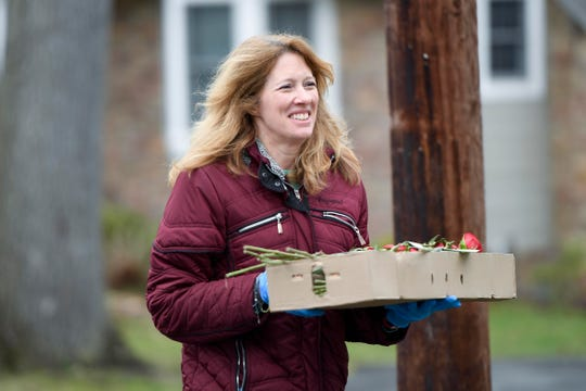 Dayna Montaina, owner of Blooms of Wayne, walks along Chestnut Drive to deliver flowers to residents on March 31.
