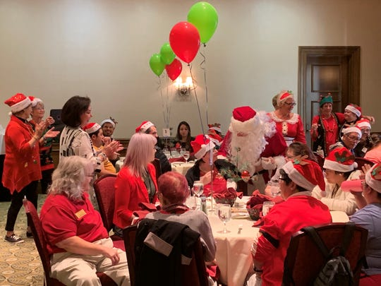 Santa Claus hands out gifts at the holiday giving luncheon for Desert Arc clients at Classic Club.