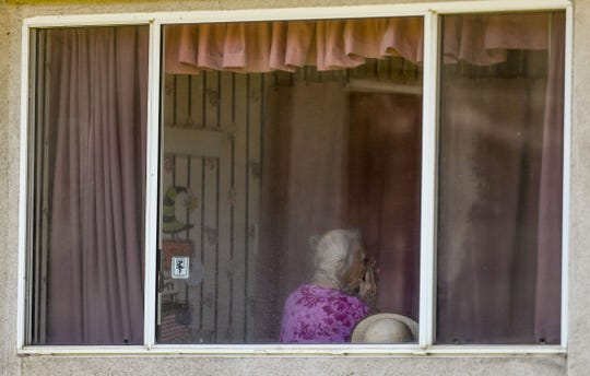 A woman places her head into her hands at the Cedar Mountain nursing home in Yucaipa where there have been more than 50 reported cases of coronavirus and two deaths, April 1, 2020.