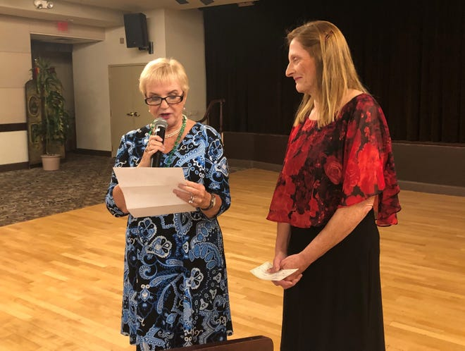 Bonnie Tucker presents Alena Callimanis with check for $4,000 to help Read With Me Volunteers purchase books for East Valley elementary students.