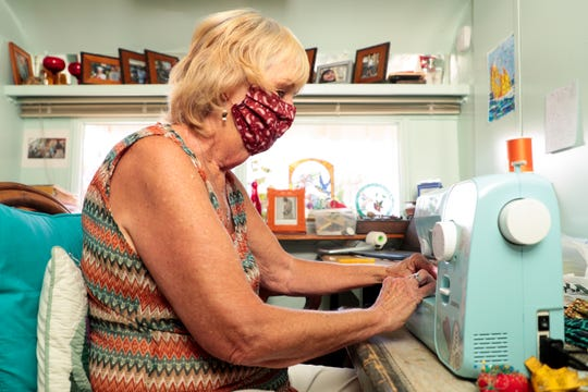 Pat Harbo sews face masks on Wednesday, April 1, 2020, while sheltering in place in her home in Palm Springs, Calif.