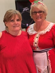 Volunteer Teddi Rozell poses with Mrs. Claus at the annual holiday giving luncheon for Desert Arc clients.