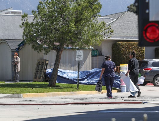 People go about their business outside of the Cedar Mountain nursing home in Yucaipa where the coronavirus has spiked among the residents there, April 1, 2020.